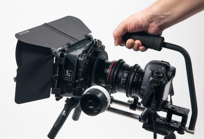 """Tiefe Perspektiven: Mit einem Tragegriff am Rig lässt man die Kamera bodennah baumeln und erhält interessante Aufnahmen aus der Froschperspektive. Vorne an der Kamera befindet sich eine """"Mattebox"""" oder auch Kompendium."""
